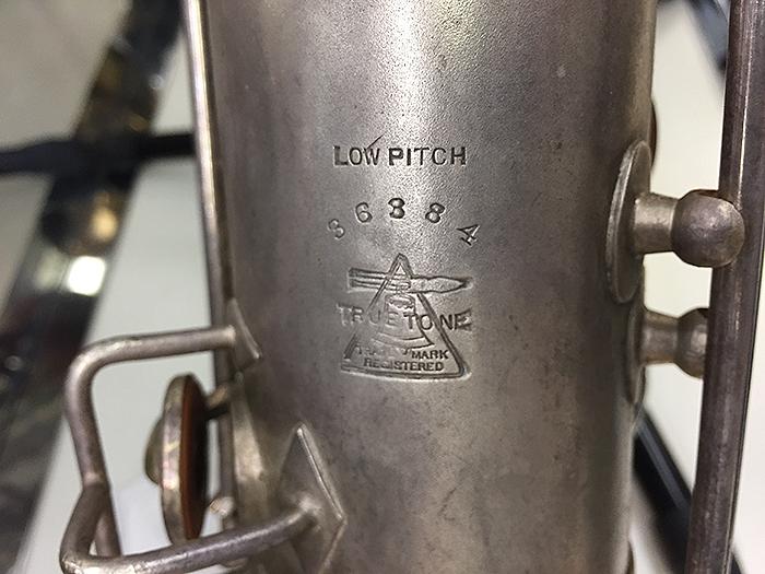 ↑アメリカン・オールド・サックスbuescherの代表的な機種「truetone」の管体刻印です。こちらはサックス買取ラボふくおか在庫のbuescher truetoneのバリトン・サックスです。